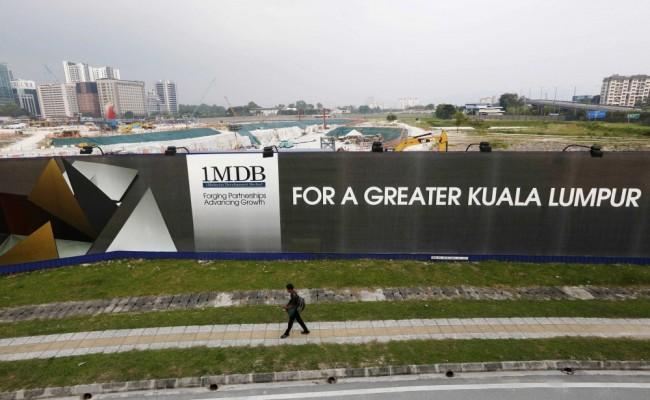 File photo of man walking past a 1 Malaysia Development Berhad billboard at the funds flagship Tun Razak Exchange development in Kuala Lumpur