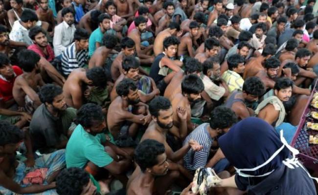 LANGKAWI 11 May 2015.Anggota Polis  memberi roti kepada pendatang asing tanpa izin(PATI)warga Bangladesh dan Myanmar yang ditahan selepas mendarat di Pantai Pasir Berdengung.NSTP/Amran Hamid